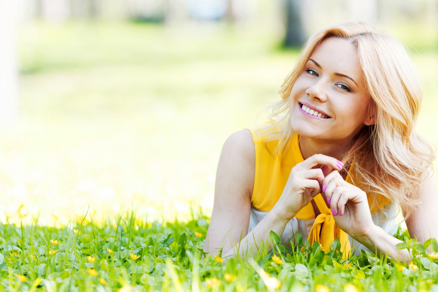 Blonde woman laying on the grass and smiling